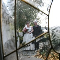 Dad and bride through the front door glass