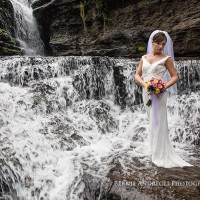 Creative Bridal Session color photograph with bride in an elegant full length pose on a rock outcrop next to a waterfall