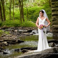 Creative Bridal Session color photograph with bride in an elegant full length pose standing on a flat rock in a stream
