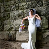 Creative Bridal Session color photograph with bride in an elegant full length pose on a sand bar under a stone railroad tressel