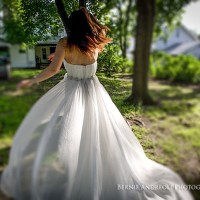 Creative Bridal Session tilt shift color photograph with bride twirling her dress in the sunlight