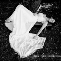 Creative Bridal Session black and white photograph with bride laying back on a bench and her bridal gown flowing to the ground