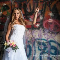 Creative Bridal Session with the Bride posing with flowers in front of a graffiti painted wall. 3/4 length portrait lit by window light