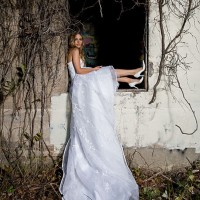 Creative Bridal Session with the Bride sitting in a window frame of an old mining building that is covered with vines